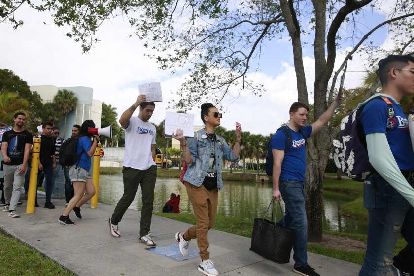 Students chant during the Bernie 2020 March to Early Vote at Florida International University to on Wednesday, March 11, 2020, in Miami. Florida and its 219 delegates could be the knockout punch for presidential hopeful Bernie Sanders after a dismal showing in the Michigan primary. The Florida primary election next Tuesday will be closely watched by people across the nation. (AP Photo/Brynn Anderson)