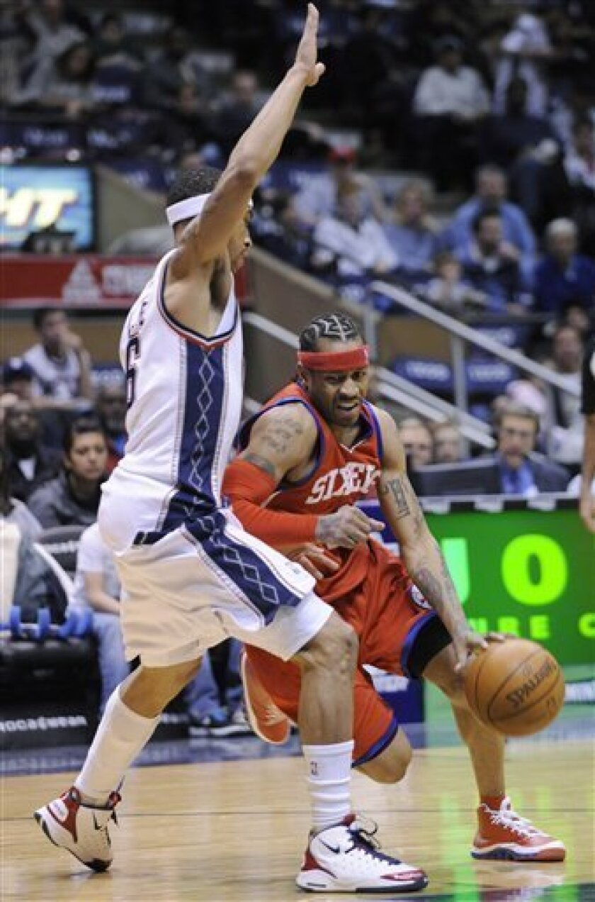 Philadelphia 76ers' Allen Iverson, right, drives to the basket as he is guarded by New Jersey Nets' Courtney Lee during the third quarter of an NBA basketball game Sunday, Jan. 31, 2010, in East Rutherford, N.J. The 76ers defeated the Nets 83-79. (AP Photo/Bill Kostroun)