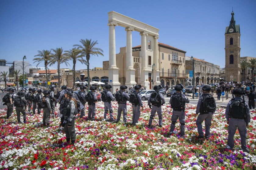 Israeli riot police stand by as Israeli Arabs protest against the decision made by the Tel Aviv-Jaffa Municipality to demolish an 18th century Muslim burial ground and build shelter for homeless people, in Tel Aviv, Israel, Friday, June 12, 2020. (AP Photo/Oded Balilty)