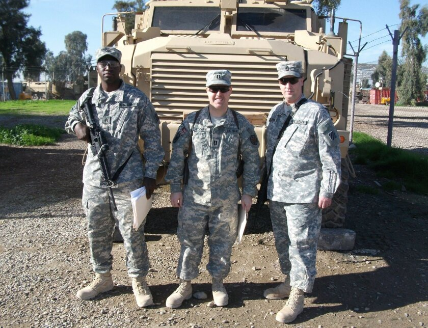 Chula Vista City Council member John McCann (center) pauses for a photo with 3rd Infantry soldiers during his service in Iraq as a lieutenant in the Navy Reserve.