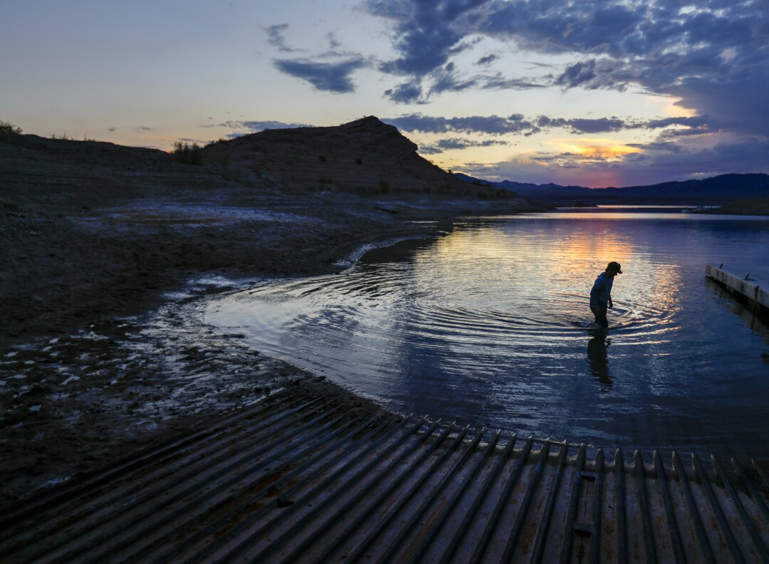 A man wades in shallow water at sunset