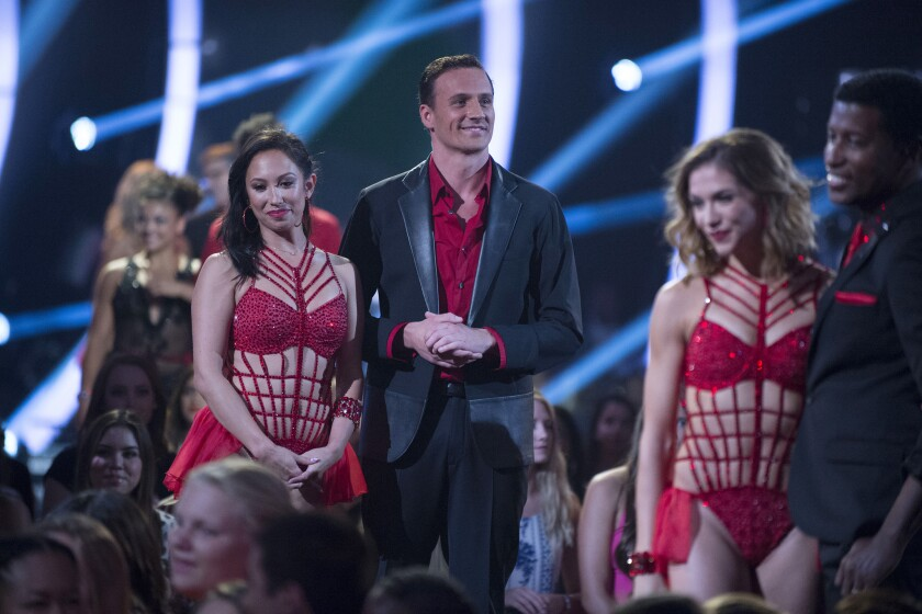 "Cheryl Burke, left, and Ryan Lochte, center, appear on ""Dancing With the Stars."" Two people were arrested Monday during a live taping of the show in Los Angeles."