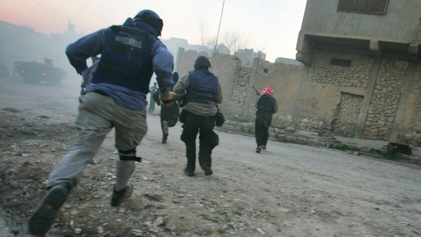 """U.S. troops and Iraqi police are shown during a firefight with insurgents in Tal Afar in January 2005 in an image from the documentary """"Hondros."""""""