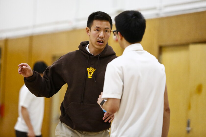 Serra head coach YY Liew speaks with a player during their match against Patrick Henry on Wednesday.