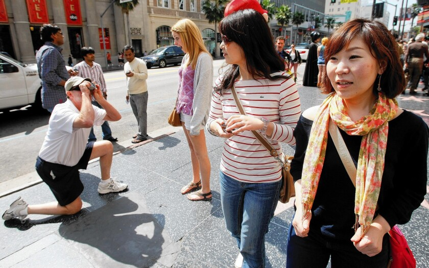 Visitors to L.A. County booked 26.6 million room nights in 2012, spent about $16.5 billion and supported 324,000 jobs in the region, according to a local tourism organization. Above, tourists Yuka Watanabe, right, and friend Miwako Tsugawa in Hollywood in 2011.