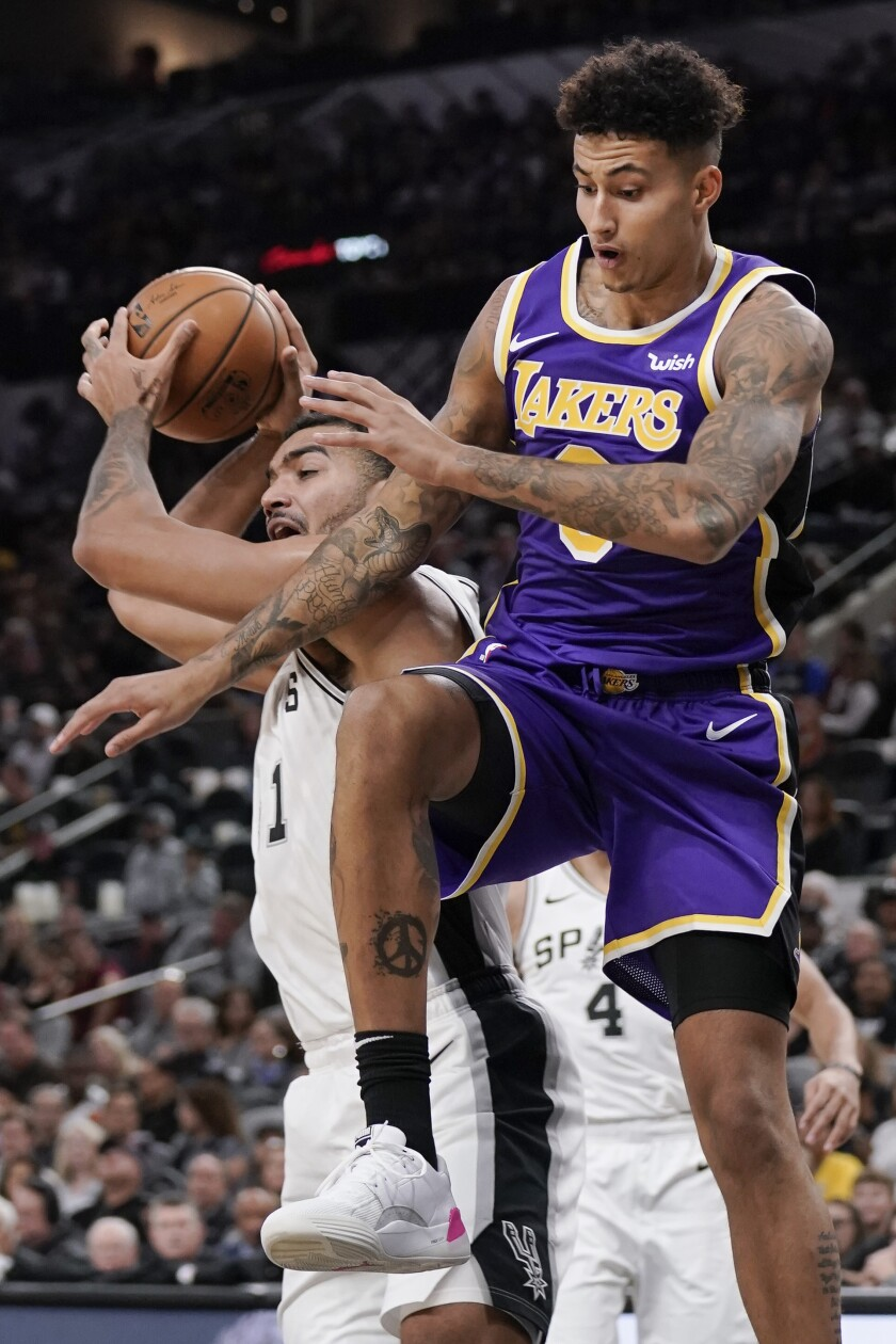 Los Angeles Lakers' Kyle Kuzma, right, collides with San Antonio Spurs' Trey Lyles during the first half of an NBA basketball game, Sunday, Nov. 3, 2019, in San Antonio. (AP Photo/Darren Abate)