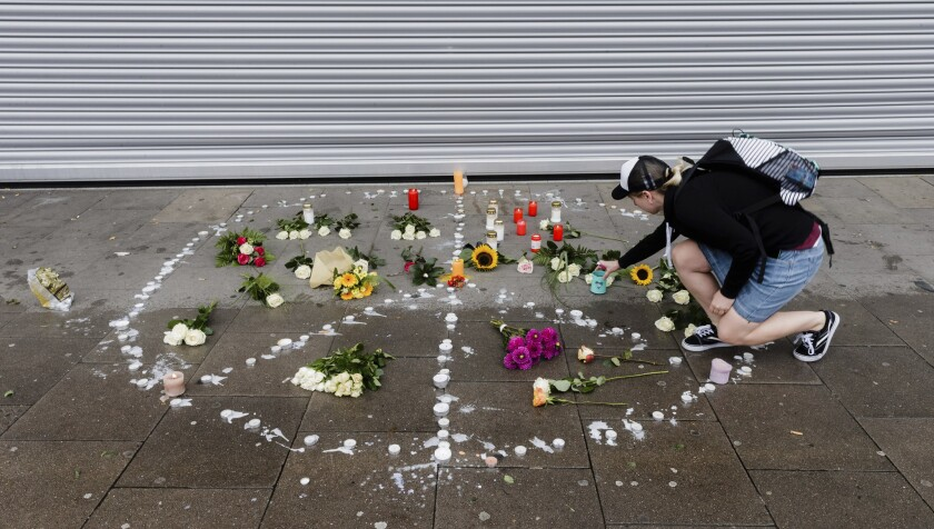 A woman places flowers near a supermarket in Hamburg, Germany, where a man armed with a kitchen knife fatally stabbed one person and injured six others.