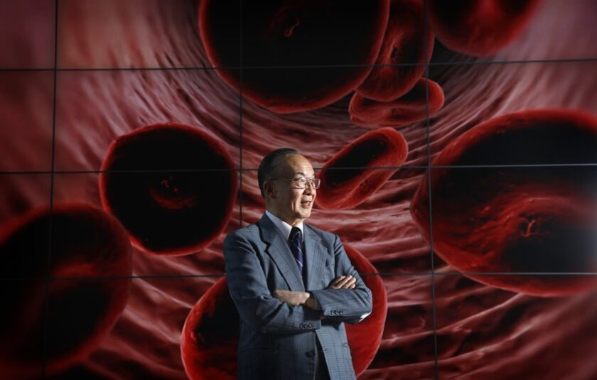 Shu Chien stands in front of image of red blood cells at UC San Diego's Jacobs School of Engineering.
