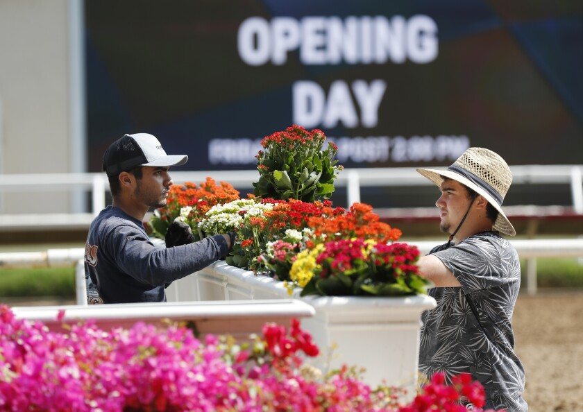 Chris Betancourt, left, and Taye Kelly arrange flowers to the winner's circle at the Del Mar Thoroughbred Club.