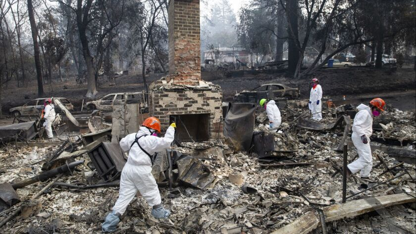 Search and rescue teams inspect the grounds of a house burned down by the Camp fire in Paradise, Calif., in November.