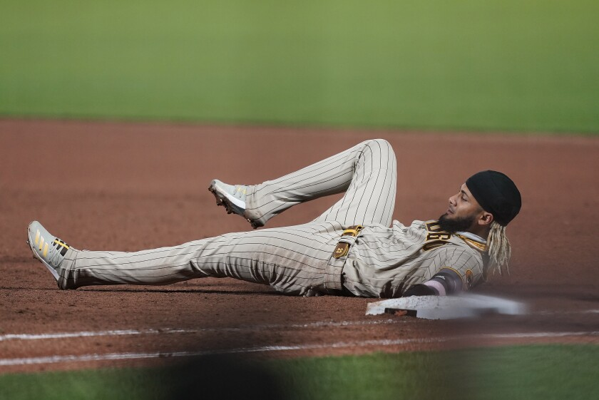 Fernando Tatis Jr. lies on the ground after being picked off at first base