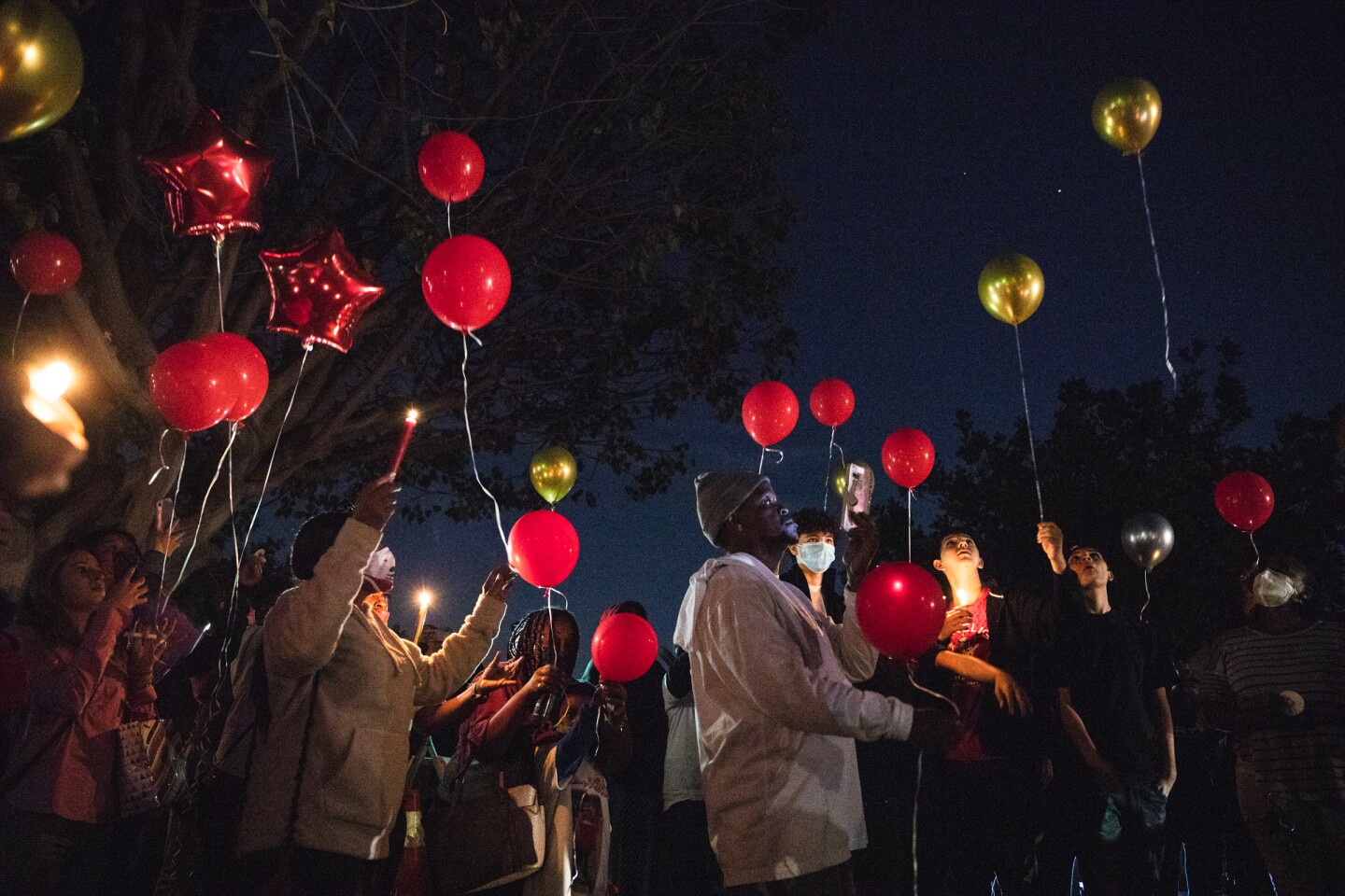 Mourners release balloons into the sky Thursday in Mount Hope during a vigil for three teens who were killed in a crash