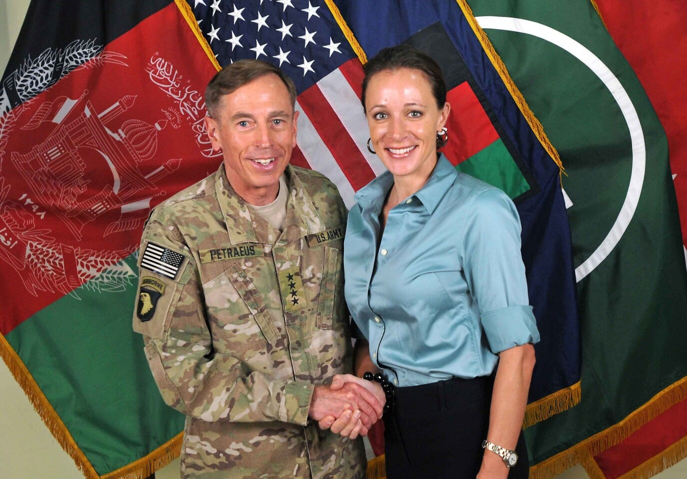 """This July 13, 2011, photo, made available on the International Security Assistance Force's Flickr website, shows Gen. David Petraeus, the former commander of U.S. forces at Afghanistan, shaking hands with Paula Broadwell, co-author of his biography """"All In: The Education of General David Petraeus."""""""