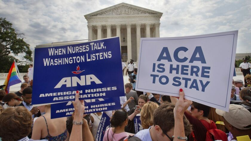 Supporters of the Affordable Care Act hold up signs as the opinion for health care is reported outsi