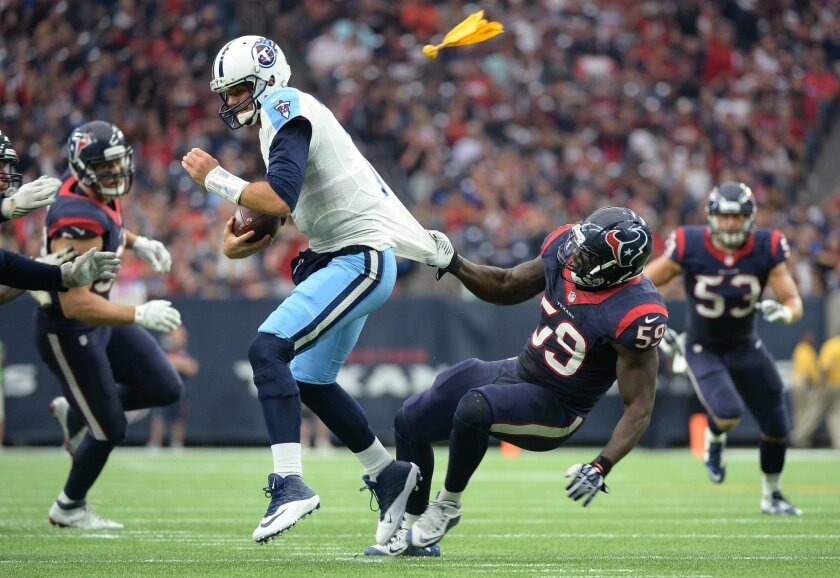 Tennessee Titans quarterback Zach Mettenberger (7) is pulled down by Houston Texans outside linebacker Whitney Mercilus (59) during the first half of an NFL football game, Sunday, Nov. 1, 2015, in Houston. A flag was thrown for a face mask call against the Houston Texans. (AP Photo/George Bridges)