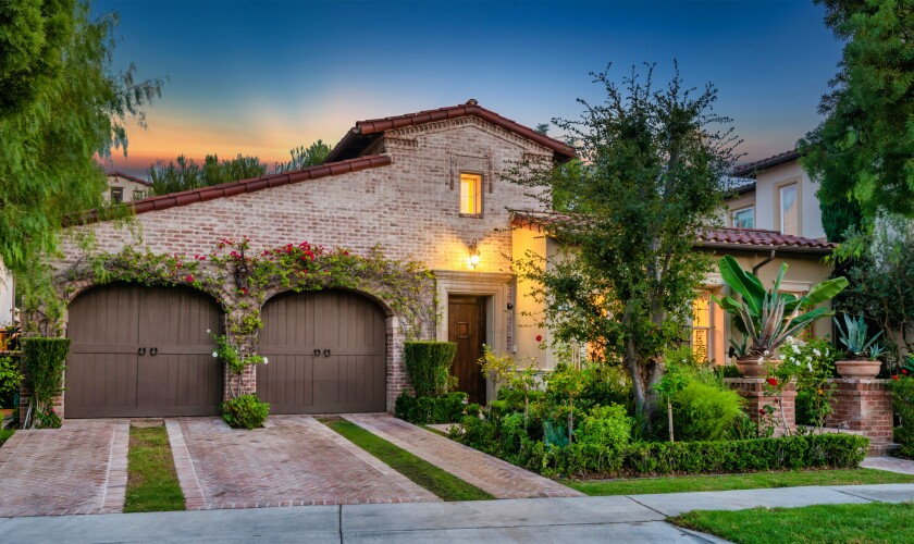 The double garage and brick exterior of the Tuscan-style home.
