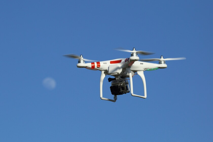 A quadcopter drone equipped with a camera. The L.A. City Council has backed Sacramento legislation that would regulate their use by civilians over wildfires and private property.