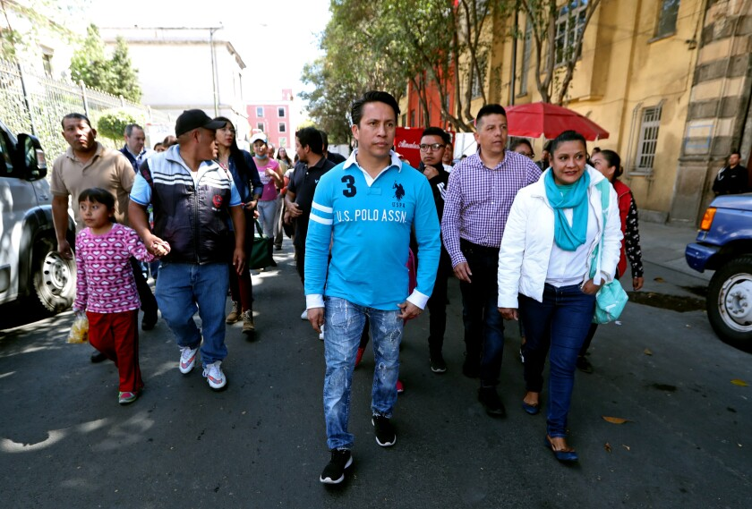 A crowd walks down a Mexico City street as parents of children with cancer protest.