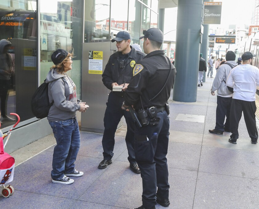 Transit officer Marc Vargas (middle), who does code compliance transit enforcement for the San Diego Metropolitan Transit System, talks with Melodi Blazi (left) on January 9, 2020 in San Diego, California. At right is transit officer Ramon Garcia who provides security for Vargas.