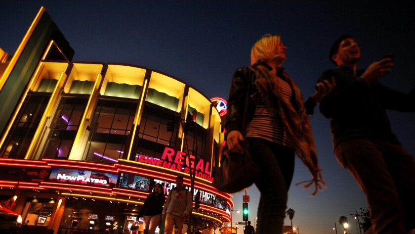 People stroll past the Regal Cinemas LA Live Stadium 14 in Los Angeles.
