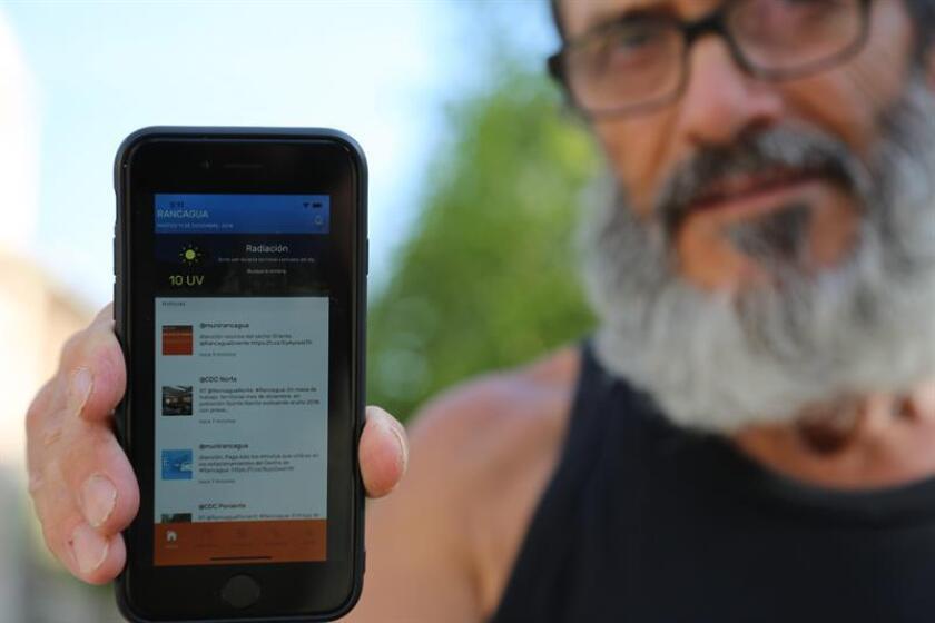 Fotografía cedida muestra a un hombre que sostiene su teléfono para mostrar la aplicación de código abierto que utiliza para acceder a servicios públicos y privados en la ciudad de Rancagua (Chile). EFE/Innova Difusión