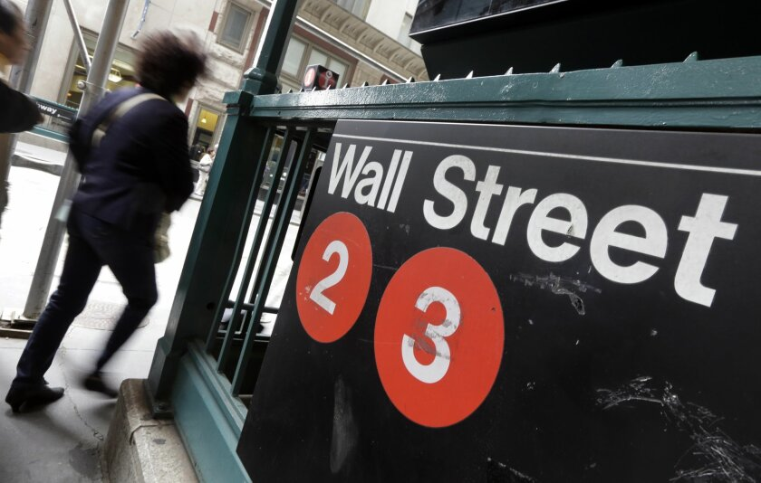 FILE - In this Oct. 2, 2014 file photo, people pass a Wall Street subway stop, in New York's Financial District. U.S. stocks rose modestly in late morning trading Wednesday, May 27, 2015, recovering part of a steep loss from the day before. Investors remain focused on Greece's debt problems. (AP Photo/Richard Drew, File)