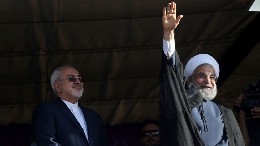 Iranian President Hassan Rouhani, right, accompanied by Foreign Minister Mohammad Javad Zarif, waves