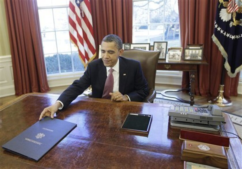 President Barack Obama signs the two-week funding bill averting a government shutdown in the Oval Office at the White House in Washington, Wednesday, March 2, 2011. The Senate on Wednesday sent President Barack Obama a Republican-drafted stopgap funding bill that trims $4 billion from the budget, c