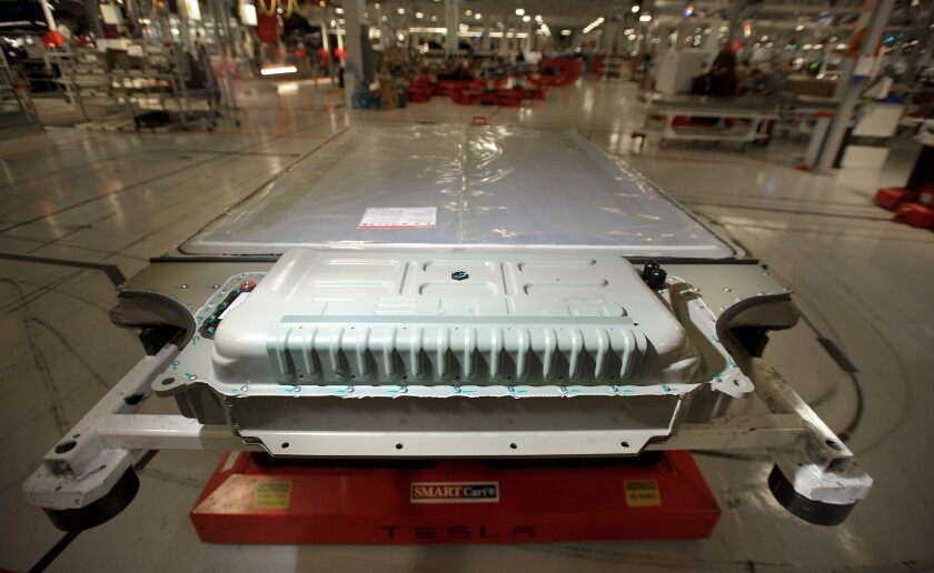 A battery awaits installation in a Tesla Model S sedan at the company's assembly plant in Fremont, Calif.