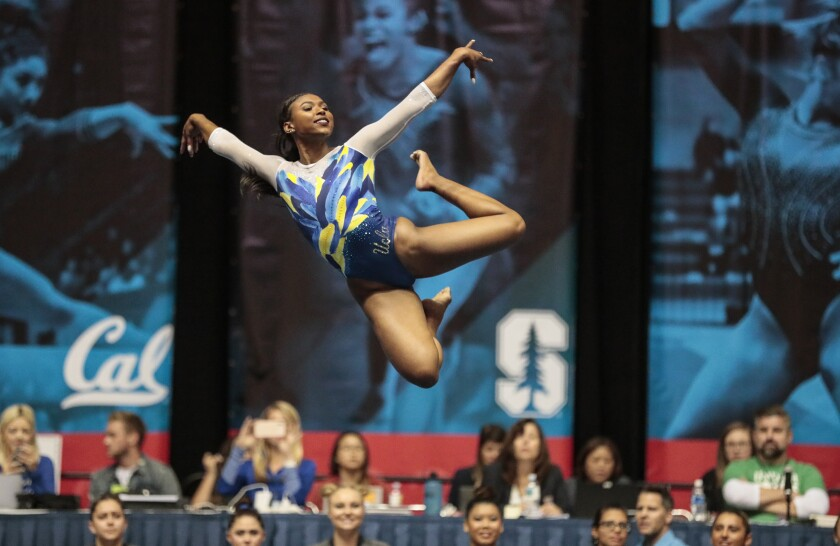UCLA gymnast Nia Dennis leaps into the air during her floor routine at the Collegiate Challenge meet at the Anaheim Convention center in January.