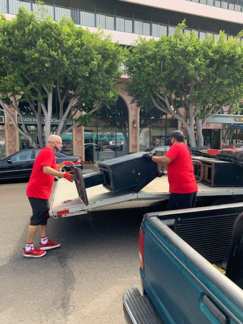 An abandoned newsstand is removed from a sidewalk in The Village as part of an effort by the La Jolla MAD.