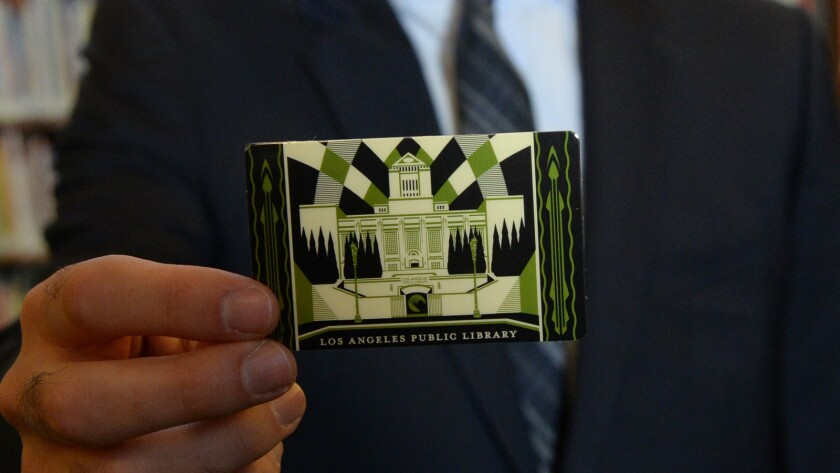 Mayor Eric Garcetti holds L.A.'s first artist-designed, limited-edition library card.