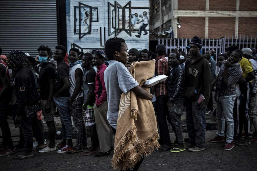 People line up for charity food distribution in Johannesburg, South Africa.