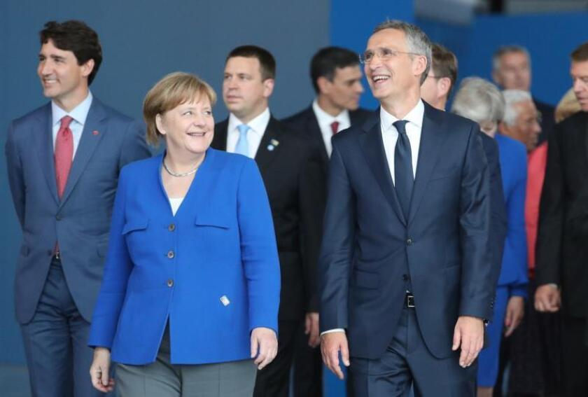 El secretario general de la OTAN, Jens Stoltenberg (dcha), conversa con la canciller alemana Angela Merkel, durante la foto de familia de la cumbre de jefes de estado de la OTAN que se celebra en Bruselas, Bélgica, el 11 de julio del 2018. EFE