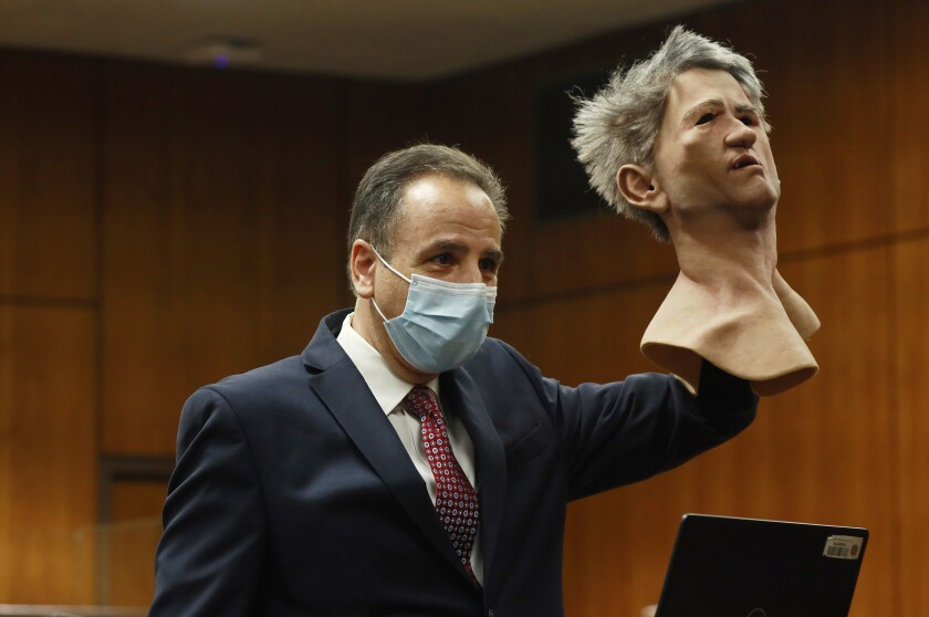 An attorney in court holds up a realistic rubber mask with gray hair