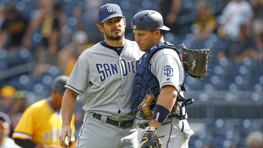 Brad Hand and A.J. Ellis embrace after the Padres beat the Pirates on Sunday in Pittsburgh.