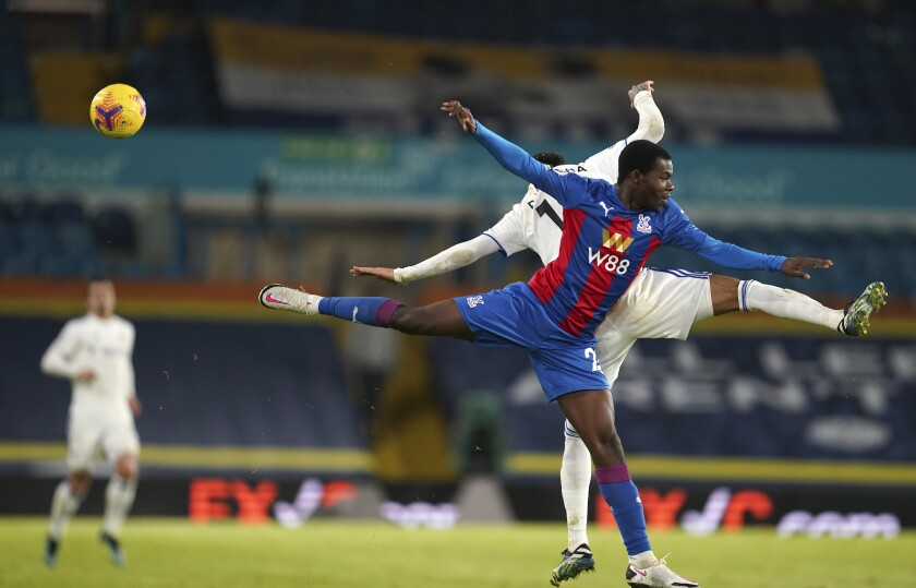 Crystal Palace's Tyrick Mitchell and Leeds United's Raphinha challenge for the ball during the English Premier League soccer match between Leeds United and Crystal Palace at Elland Road Stadium in Leeds, England, Monday, Feb. 8, 2021. (AP Photo/Jon Super, Pool)