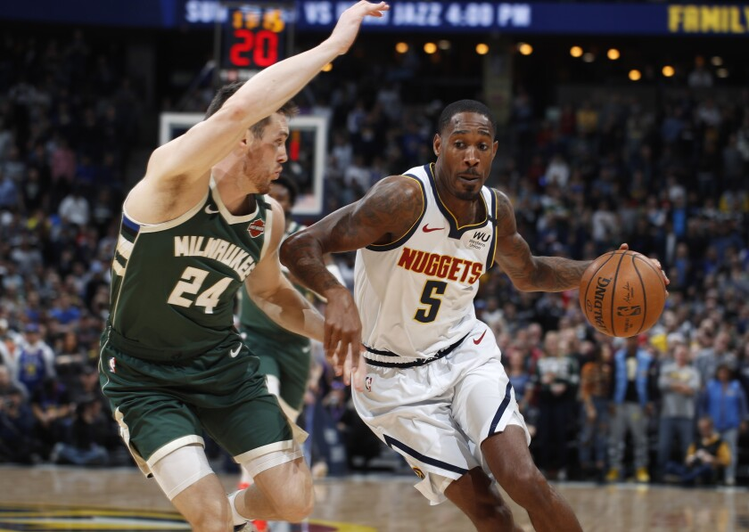 Denver Nuggets forward Will Barton, right, drives to the basket past Milwaukee Bucks guard Pat Connaughton in the first half of an NBA basketball game Monday, March 9, 2020, in Denver. (AP Photo/David Zalubowski)