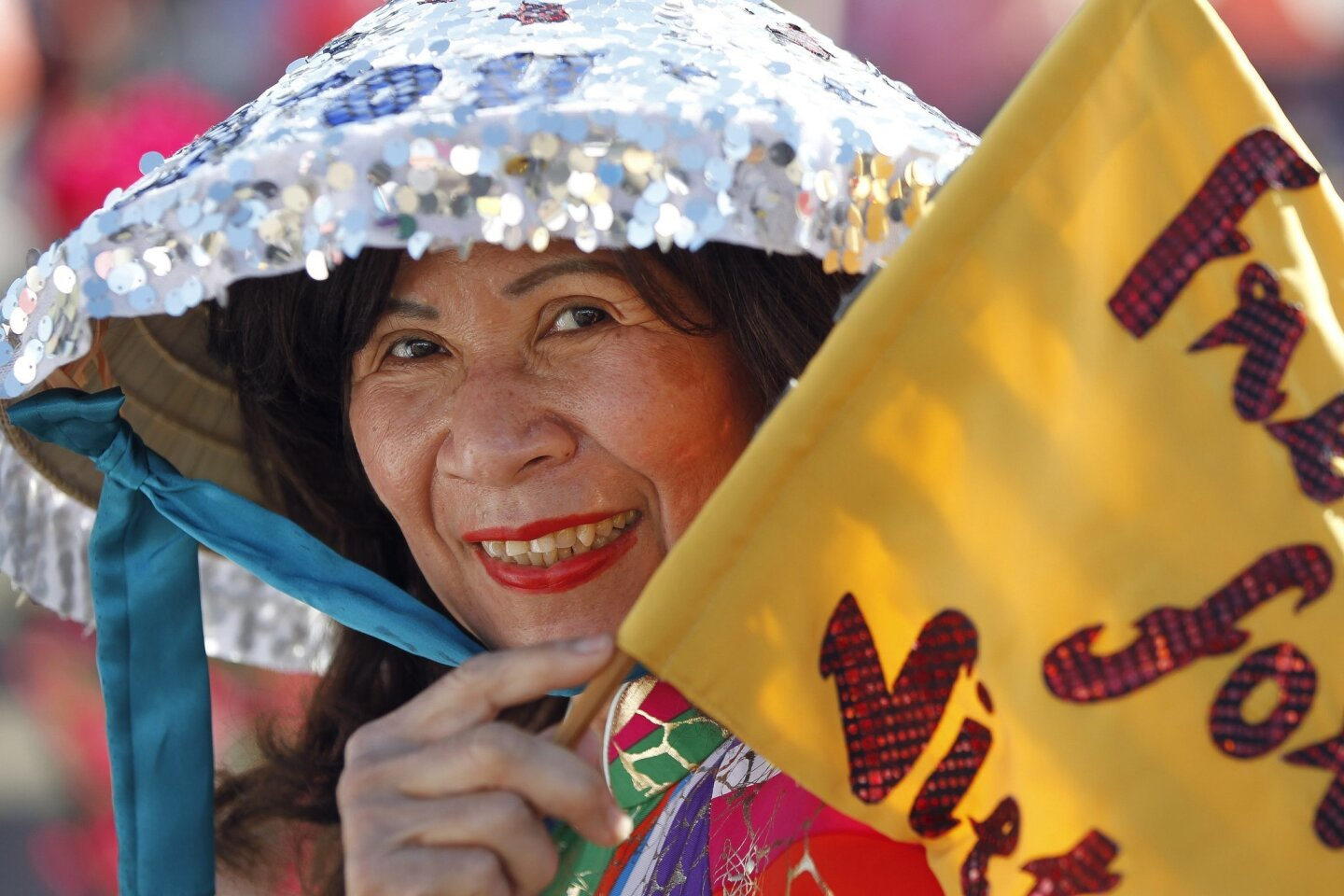 """Tam Pham carries her flag that says """"Freedom for Vietnam"""" during the Little Saigon San Diego Foundation's annual Lunar New Year celebration at the Qualcomm Stadium parking lot in San Diego on Saturday, February 14, 2015."""