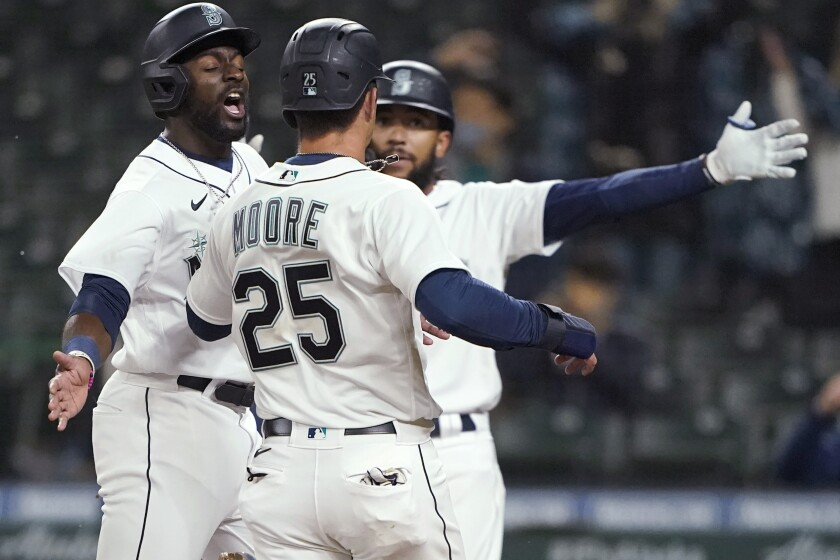 Seattle Mariners' Taylor Trammell, left, greets Dylan Moore (25) at the plate after they scored during the eighth inning of the team's baseball game against the San Francisco Giants, Thursday, April 1, 2021, in Seattle. (AP Photo/Ted S. Warren)