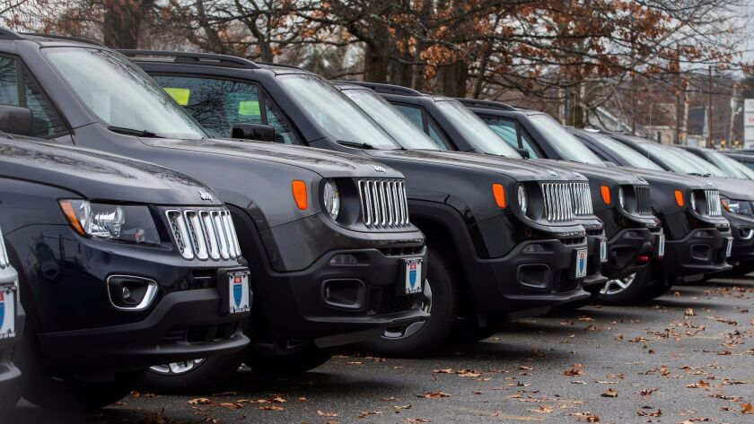 Jeep vehicles sit on a dealership lot in Lowell, Mass.
