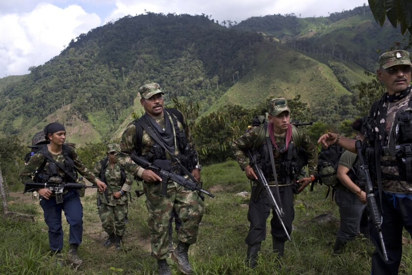 Juan Pablo, center, a commander of the Revolutionary Armed Forces of Colombia, or FARC, walks with his comrades in Antioquia state in January.