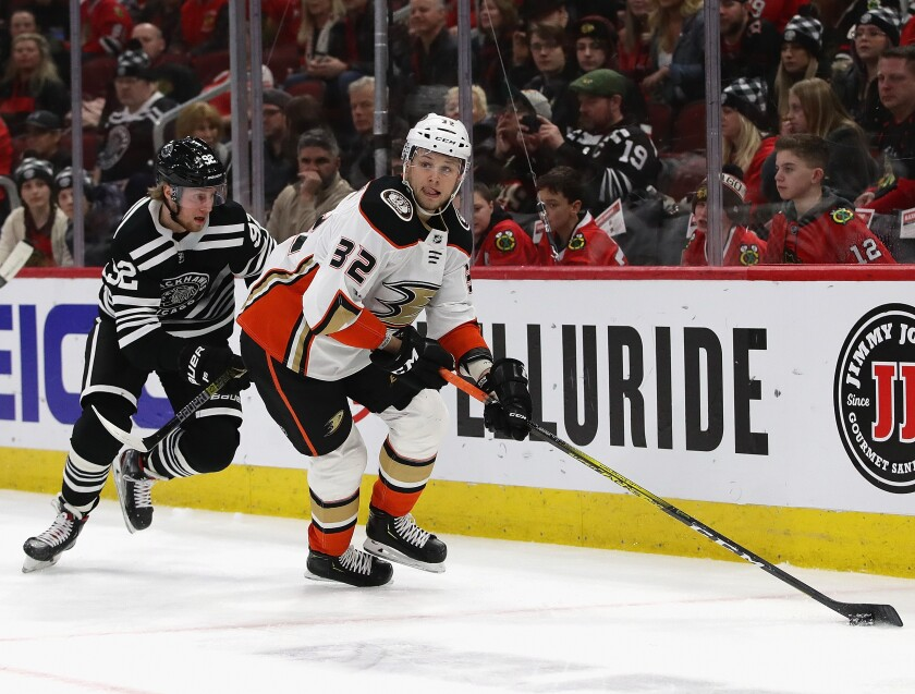 Ducks' Jacob Larsson (32) looks to pass under pressure from Chicago Blackhawks' Alex Nylander (92) on Tuesday in Chicago.