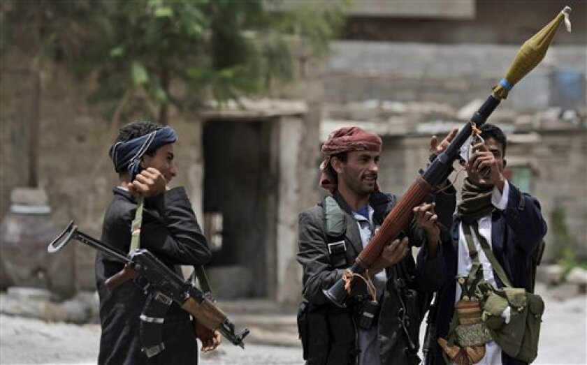 An armed tribesman, loyal to Sheik Sadeq al-Ahmar, the head of the powerful Hashid tribe, hands his colleague an RPG launcher, while standing guard around al-Ahmar's house in Sanaa, Yemen, Saturday, June 11, 2011. Nearly 100,000 Yemenis protested Friday in a main square of the capital, demanding the president's ouster in the biggest rally since Ali Abdullah Saleh left for Saudi Arabia after he was wounded in an attack on his palace. (AP Photo/Hani Mohammed)
