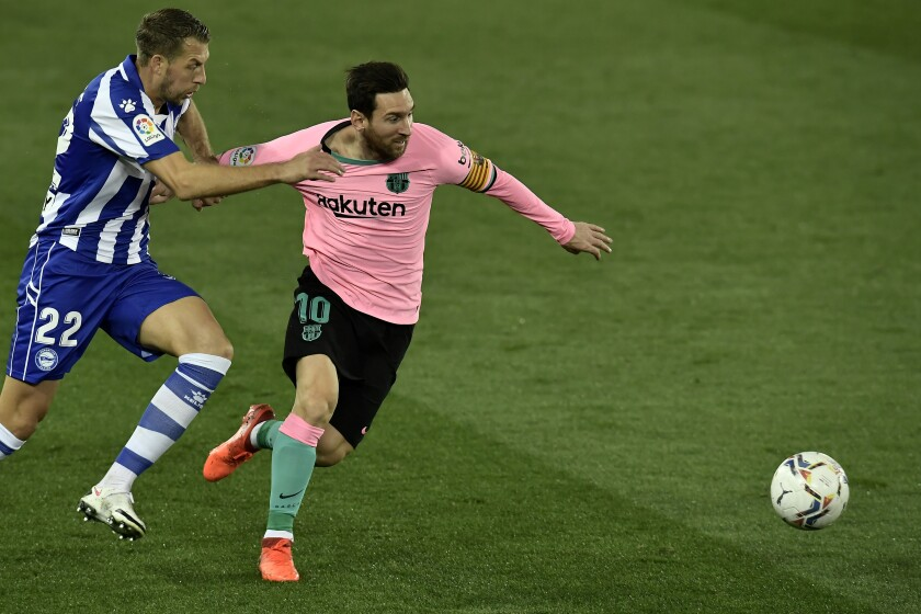Barcelona's Lionel Messi, right, vies for the ball with Alaves' Florian Lejeune during the Spanish La Liga soccer match between Alaves and Barcelona at Mendizorroza stadium in Vitoria, Spain, Saturday, Oct. 31, 2020. (AP Photo/Alvaro Barrientos)