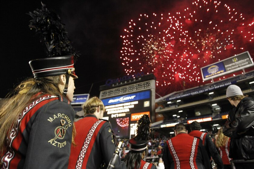 Members of the Aztecs marching band watch a fireworks display at halftime of the San Diego County Credit Union bowl game at Qualcomm Stadium.