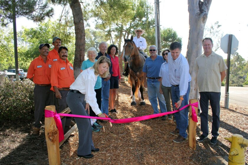 RSF Association trails committee member Daniel Bunn and Suzy Halleland from the Village Church cut the ribbon on the new trail on Las Colinas. Attending the ribbon cutting were Association maintenance staff members, resident and pedestrian Joan Voelz, trails committee members Brent Clark and Rochel