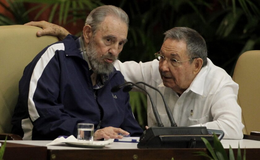 FILE - In this April 19, 2011 file photo, Fidel Castro, left, and Cuba's President Raul Castro talk during the 6th Communist Party Congress in Havana, Cuba. Some party members are calling for the April 2016 congress to be postponed to allow public debate about the governmentís plans to continue market-oriented reforms of Cubaís centrally controlled economy. (AP Photo/Javier Galeano, File)