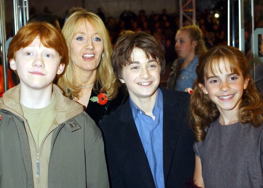 J.K. Rowling in 2001 with the then-young stars of the Harry Potter film franchise, from left: Rupert Grint (Ron), Daniel Radcliffe (Harry) and Emma Watson (Hermione). In a coming interview, Rowling is said to have reconsidered the Hermione-Ron romance.
