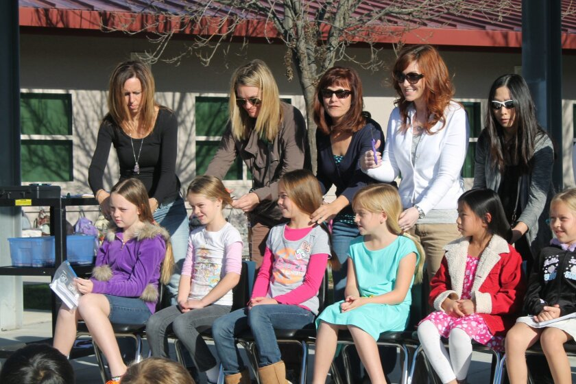 Stone Ranch Elementary students (from left) Haley, Louisa, Nicole, Kate, Kayley, and Nina, with their mothers and third-grade teacher Kelly Lasho (second from right), prepare for haircuts Feb. 27 to donate ponytails to Locks of Love.